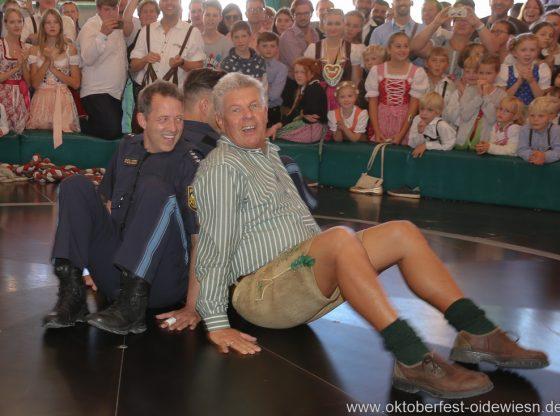 Oberbürgermeister Dieter Reiter misst sich mit Polizisten der Wiesnwache auf dem Teufelsrad